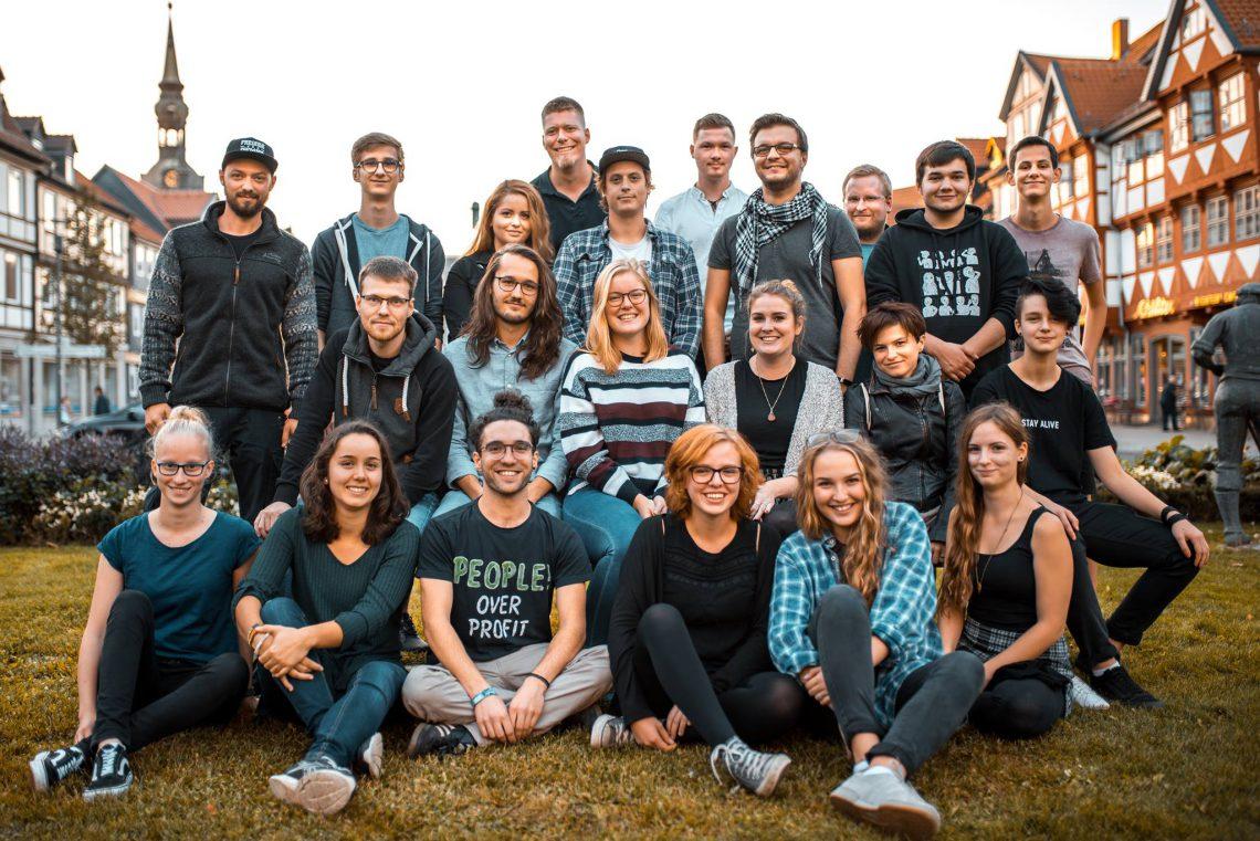 Gruppe von jungen Menschen auf einer Wiese.