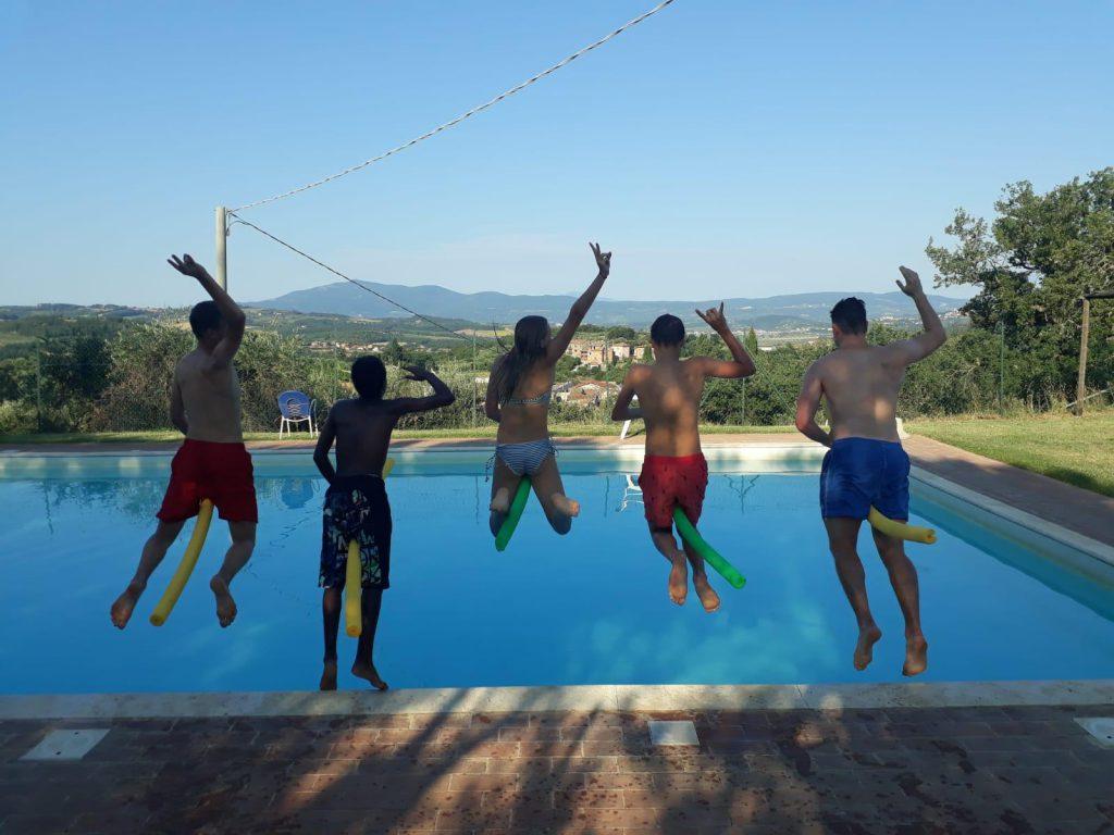 Fünf Jugendliche, die mit Poolnudeln in einen Pool springen.