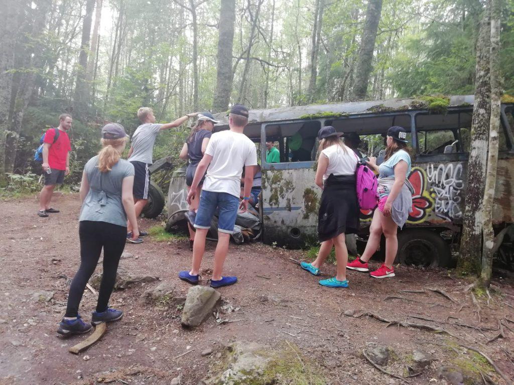 Mehrere Jugendliche vor einem alten besprühten und bewachsenen Bus ohne Reifen im Wald.