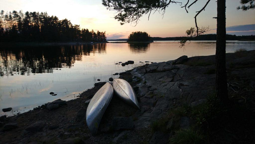 Zwei Kanus, die in der Abenddämmerung am Fluss liegen.