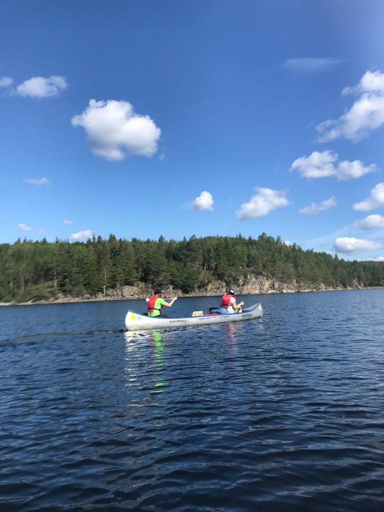 Zwei Menschen mit Paddeln und Schwimmwesten in einem Kanu auf dem Wasser. Dahinter ein bewaldeter Berg.