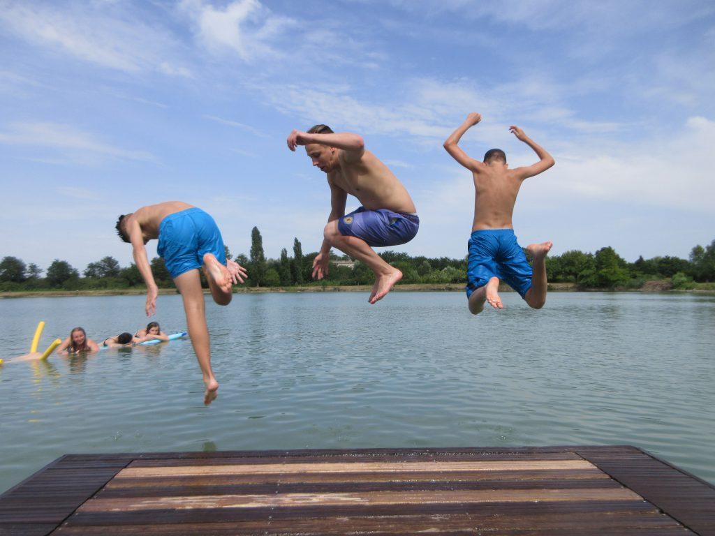 Drei Jungen, die gleichzeitig von einem Steg ins Wasser springen.