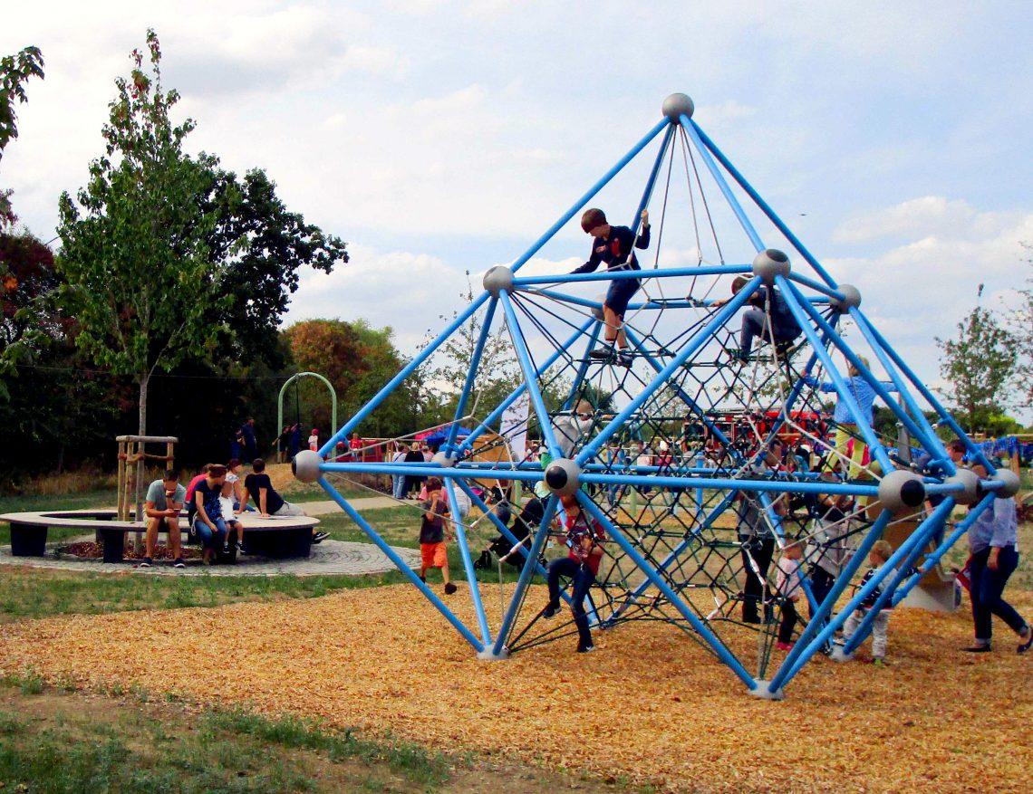 Mehrere Kinder, die auf einem Spielplatz auf einem Klettergerüst klettern. Im Hintergrund eine runde Holzbank um einen Baum und eine Seilbahn an der auch Kinder spielen.
