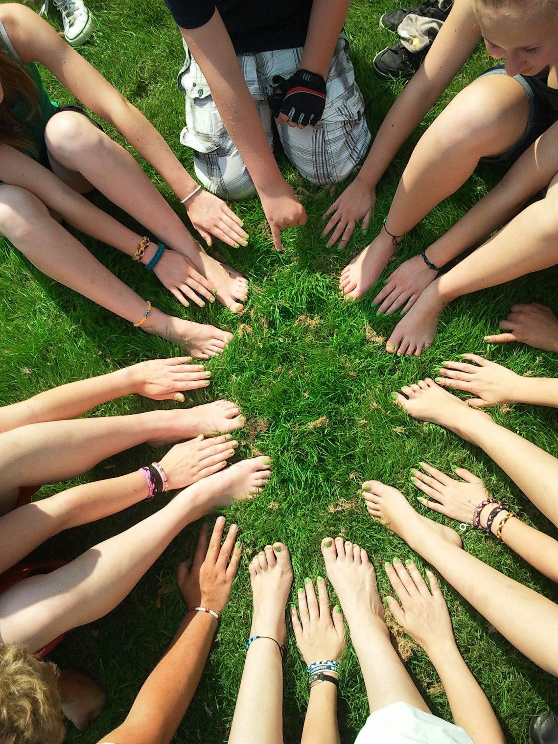 Acht Jugendliche, die auf Grünem Gras alle ihre Hände und nackten Füße in die Mitte strecken, die alle grün lackierte Nägel haben.