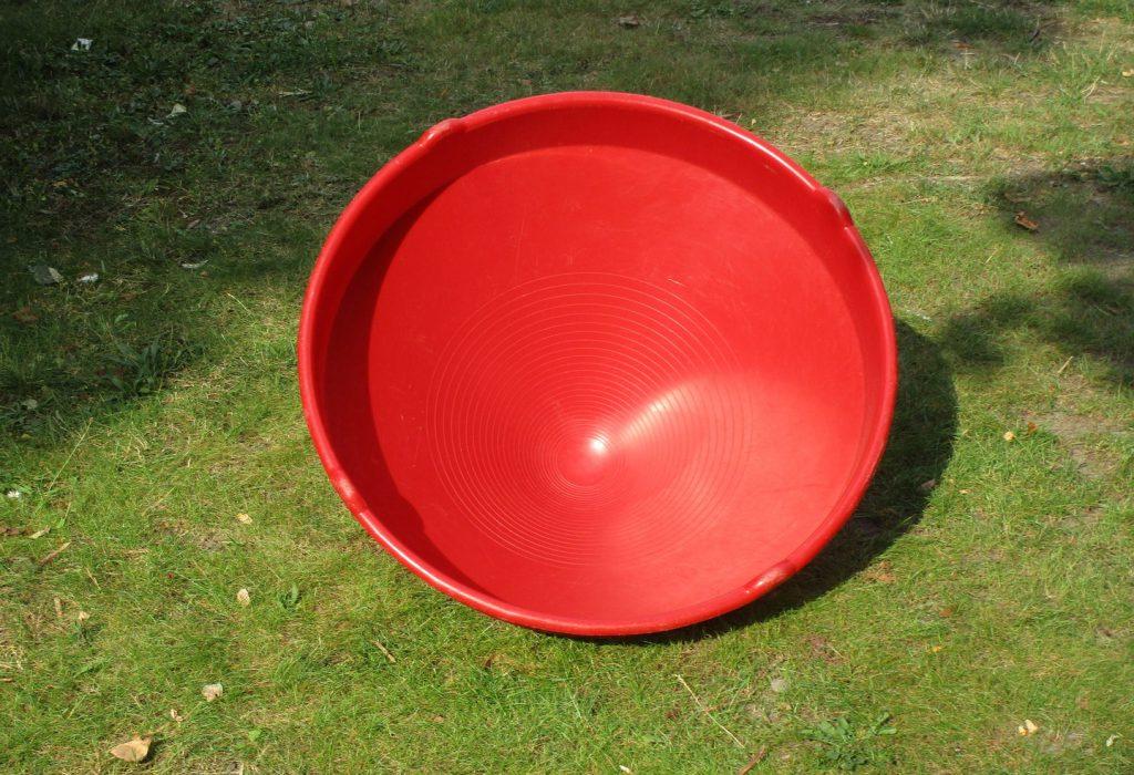 rote Plastikhalbkugel auf dem Rasen liegend